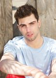 Handsome male fashion model sitting outdoors. Portrait of a handsome male fashion model sitting outdoors Royalty Free Stock Photo