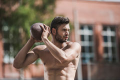 Handsome male football player with ball on court