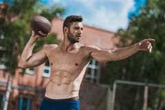 Handsome male football player with ball on court. Young handsome male football player with ball on court Stock Photography