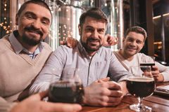 Handsome male friends sitting together. Saturday night. Handsome cheerful male friends sitting together at the table and smiling while looking at you Royalty Free Stock Photos