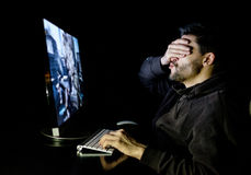 Handsome male gamer playing computer video game. At the table in dark room Royalty Free Stock Photo