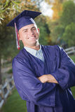 Handsome Male Graduate in Cap and Gown Stock Photo