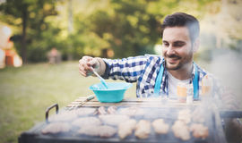 Handsome male grilling meat outdoor. Handsome male grilling meat for barbecue party outdoor Royalty Free Stock Photos