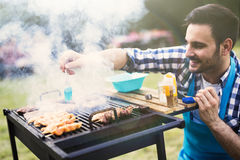 Handsome male grilling meat outdoor stock images