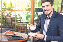 Handsome male has a french breakfast at cafe restaurant Stock Images