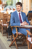Handsome male has a french breakfast at sidewalk cafe stock photography