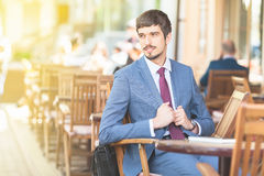 Handsome male has a french breakfast at sidewalk cafe outdors. Good morning. Smiling businesman. Elegant succesful man. Has a mustache Royalty Free Stock Photo