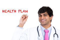 Handsome male health care professional or doctor or nurse writing the words 'Health Plan' Stock Images
