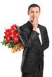 Handsome male hiding a bouquet of flowers. And gesturing silence isolated on white background Stock Photography