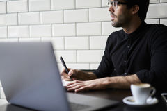 Handsome male hipster journalist. Thinking over his reportage writing down best ideas into notebook creating article for publication working hard in morning Stock Photography