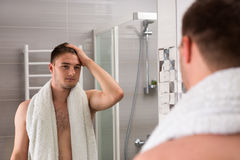 Handsome male holding towel on his shoulders while looking in th. Handsome male holding towel on his shoulders after washing procedures while looking in the Royalty Free Stock Images