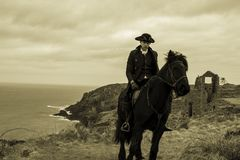 Handsome Male Horse Rider Regency 18th Century Poldark Costume with tin mine ruins and Atlantic ocean in background. Riding black stallion, horse royalty free stock photo