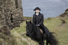 Handsome Male Horse Rider Regency 18th Century Poldark Costume with tin mine ruins and Atlantic ocean in background. Riding black stallion, horse Royalty Free Stock Photos