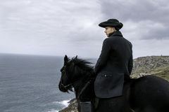 Handsome Male Horse Rider Regency 18th Century Poldark Costume with tin mine ruins and Atlantic ocean in background. Riding black stallion, horse stock images