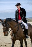 Handsome Male Horse Rider riding horse on beach in traditional clothing Stock Photo
