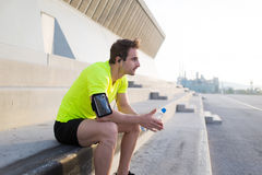 Handsome male jogger hold bottle of water and taking break after morning workout Royalty Free Stock Images