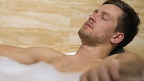 Handsome male lying in bathtub enjoying pleasant moments, meditation and leisure