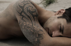 Handsome male lying on the sand. Handsome tattooed male lying on the sand Stock Photo