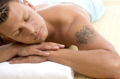 Handsome male lying in spa resort Stock Photos
