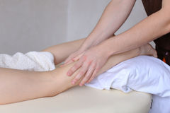Handsome male massage therapist performs procedure for girl`s le Royalty Free Stock Photo