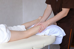 Handsome male massage therapist performs procedure for girl`s le Royalty Free Stock Image