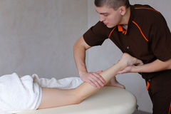 Handsome male massage therapist performs procedure for girl`s le Stock Photos