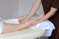 Handsome male massage therapist performs procedure for girl`s le Royalty Free Stock Images