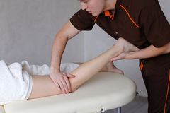 Handsome male massage therapist performs procedure for girl`s le Stock Photography