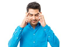 Male Massaging Temples During Headache Against White Background. Handsome male massaging temples during headache against white background royalty free stock photography