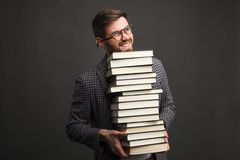 Young man loaded with books. Handsome male model in glasses holding stack of heavy books on gray background Stock Photography