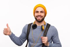 Cheerful hipster hitchhiking cheerfully on white Stock Photography