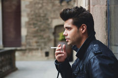 Handsome male model holding cigarette in the hand looking pensive and serious. Side shot view of fashionable young man smoking the cigarette while looking into Royalty Free Stock Image