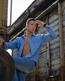 Handsome male model looking far. Fit guy with shirt open looking in the distance hanging from old train Stock Image
