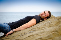 Handsome male model lying on sea rock Stock Images