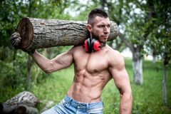 Handsome male model moving logs, cutting firewood Stock Photo