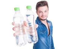 Handsome male model offering two bottles of cold water Stock Images