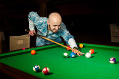 Handsome male model plays at pool billiard table Stock Photo