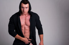 Handsome male model posing naked wearing a hoodie Royalty Free Stock Images