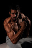 Handsome male model posing and showing his arm muscles Royalty Free Stock Photography