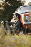 Handsome male model relaxing next to the car Royalty Free Stock Image