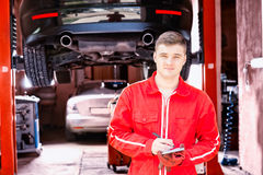 Handsome male motor mechanic standing making notes Royalty Free Stock Photo