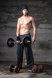 A handsome male with no shirt on. Lifting weights Stock Photography