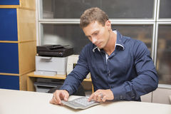Handsome male office worker using calculator Stock Photos