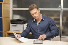 Handsome male office worker using calculator Stock Image
