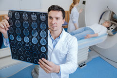Handsome male oncologist working in the medical lab. MRI scan. Handsome nice male oncologist standing in the medical lab and looking at the MRI scan images while royalty free stock image