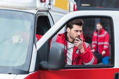 Handsome male paramedic talking by portable radio and standing close. To ambulance stock images