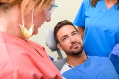 A handsome male patient waiting to receive a dental treatment in a dental studio Stock Images