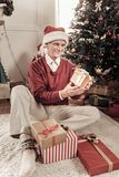 Handsome male person celebrating New Year. Happy manhood. Delighted pensioner keeping smile on his face and looking forward while sitting under Christmas tree Royalty Free Stock Photo