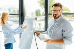 Handsome male person holding computer. I will look. Positive delighted brunette keeping smile on his face and standing in semi position while looking at camera Stock Photography