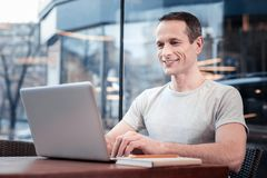Handsome male person typing message. Modern technologies. Cheerful brunette keeping smile on his face and holding hands on keyboard while looking at screen of Stock Image
